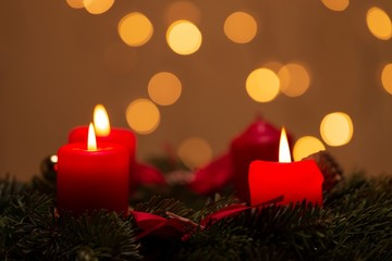 Four burning red Advent candles with bokeh