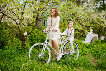 young mother of son sit together playing actively having fun on white old bike in blooming garden spring flowers during summer holidays.