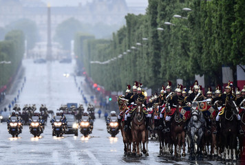Mounted Republican guards ride down the Champs-Elysees Avenue in front of French President's Emmanuel Macron's car arriving for a ceremony to mark the end of World War II in Paris