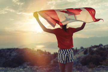 Happy child teenage girl waving the flag of Canada while running at sunset Fototapete