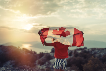 Happy child teenage girl waving the flag of Canada while running at sunset