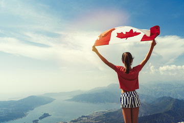 Photo sur cadre textile Canada Child girl is waving Canadian flag on top of mountain at sky background