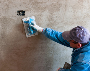 Worker lays out the first layer of rough plaster on which the plaster will then be made with a plaster finish. Selective focus