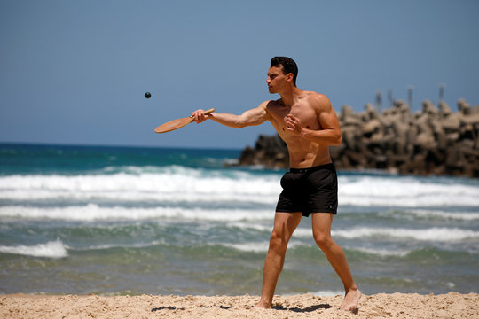 """A man plays paddle ball, known in Hebrew as """"matkot"""", a popular Israeli sport, at a beach in Ashkelon, Israel"""