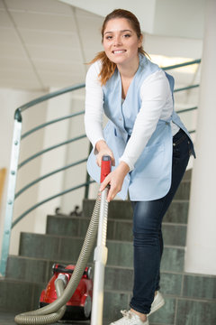 young woman cleaning the house with vacuum cleaner