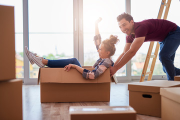 Playful couple having fun with boxes during move house
