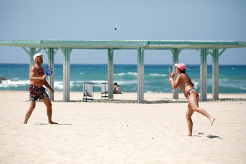 """People play paddle ball, known in Hebrew as """"matkot"""", a popular Israeli sport, at a beach in Ashkelon, Israel"""