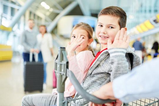 Winkende Kinder freuen sich auf den Urlaub