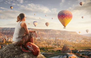 Wall Mural - Happy woman traveler watching the hot air balloons at the hill of Cappadocia, Turkey.