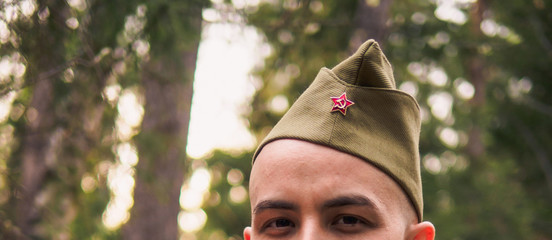 View of man in soviet war uniform in forest. Victory day reenactment