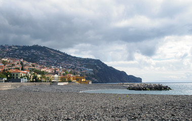a view of the beach at funchal with coastal city buildings and surrounding hills