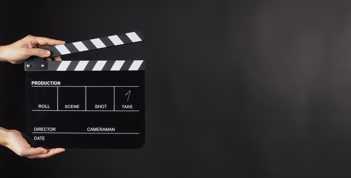 Hand is holding Black clapperboard or movie slate on black background.It have write in number.