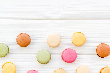 Macarons design on white wooden background top view space for text