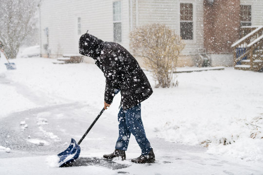 Man abstract in winter coat cleaning shoveling driveway street from snow in heavy snowing snowstorm holding shovel by residential house