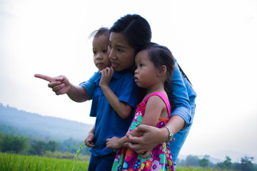 Happy Mother and her child play outdoors having fun, and pointing at something in the Green rice field.