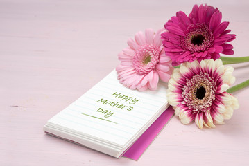 three gerbera flowers lying on a writing pad, pastel pink colored background with copy space, text Happy Mother's Day