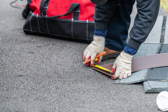Closeup of construction man hands measuring roof shingles with yellow tape on asphalt ground driveway street