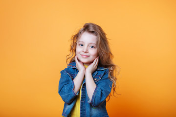 Studio portrait of smiling little girl on a yellow background Fototapete
