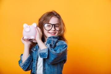 Happy girl shaking piggy box on orange background Wall mural