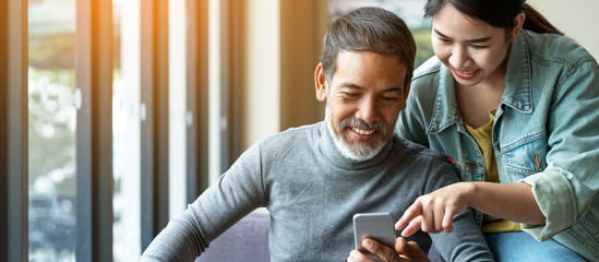 Smile attractive stylish short beard mature asian man using smartphone with young woman. Daughter teach asian old man or dad using internet social media network technology with digital gadget at home. Fotomurales