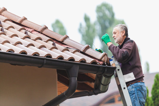 Man repairs a tiled roof of house close up