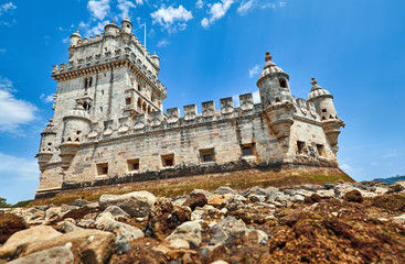 Fototapete - Lisbon, Portugal. Tower Belem at coast of river Tagus. Stones and mussels day during low tide blue sky with clouds.