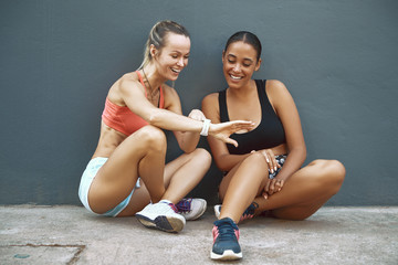 Wall Mural - Smiling friends checking a sports watch during their workout bre