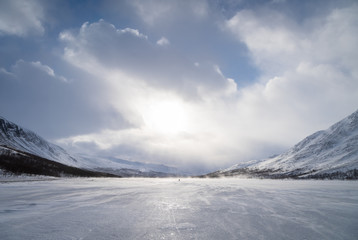 High winds for a cross-country skier with sled (pulka) on a frozen river in Lapland, Sweden.
