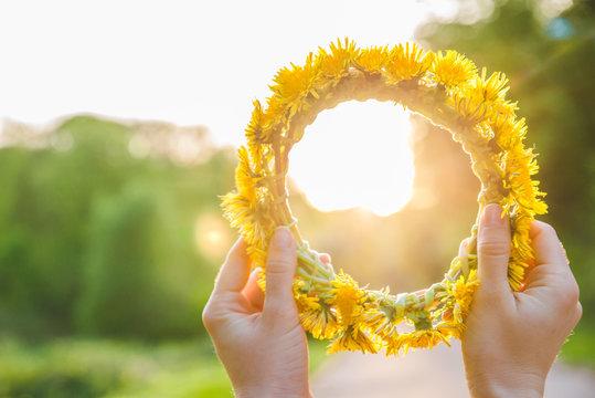woman hand holding wreath of yellow dandelions