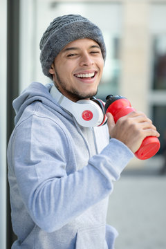 Smiling young latin man drinking sports training portrait format fitness winter