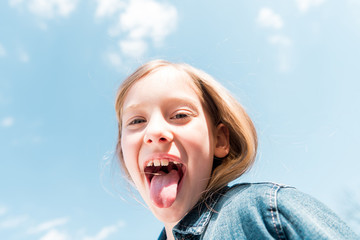 low angle view of happy kid showing tongue under sky