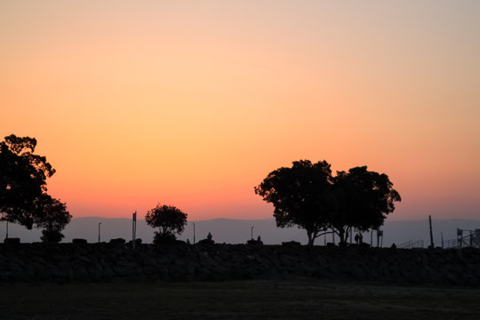 Stunning sunrise view at the Sea of Galilee with silhouette of trees and tourists