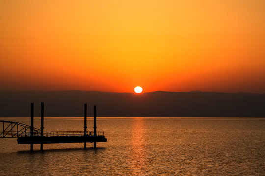 Sun rises over mountains alongside the Sea of Galilee