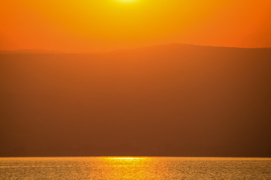 Sunrise fully covering the scene of Sea of Galilee and mountains of Galilea