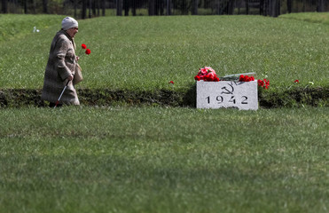 A woman carries flowers at the Piskaryovskoye Memorial Cemetery on the eve of the Victory Day in Saint Petersburg