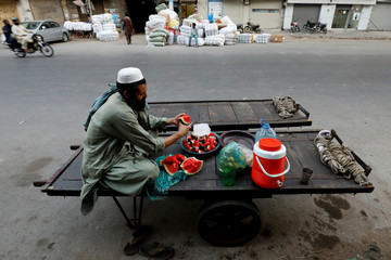 A labourer prepares fruit plates on his push cart before breaking fast during the fasting month of Ramadan along a road in Karachi