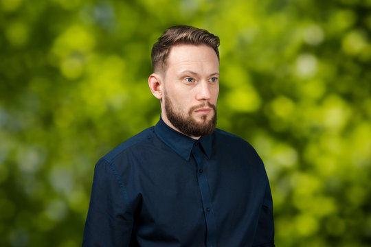 Portrait of handsome serious adult man on green bokeh background. Caucasian man with beard. Businessman.