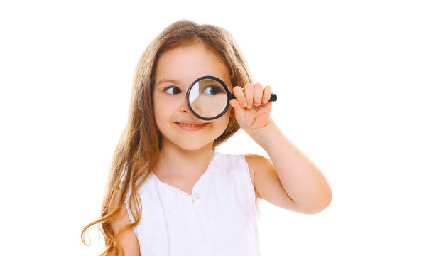 Portrait close-up little girl child looking through magnifying glass isolated on white background