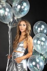 Pretty young woman with silver party balloons.