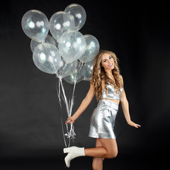 Pretty young woman dancing with silver party balloons.