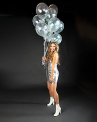 Pretty young woman in flirty pose with silver party balloons.