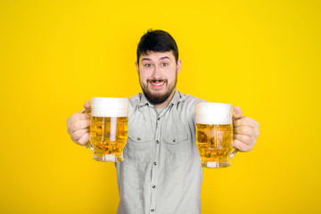 cheerful man offers the viewer a glasses of beer, image over yellow background