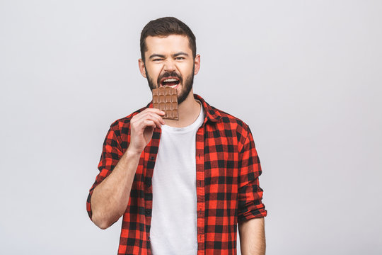 Young handsome man eating chocolate bar isolated against white background with a happy face standing and smiling with a confident smile showing teeth.