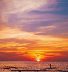 Tropical colorful dramatic sunset with cloudy sky . Evening calm on the Gulf of Thailand. Bright afterglow. Silhouette of swimming man on the water
