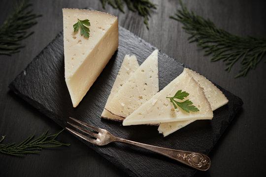 Sliced cured cheese on black slate