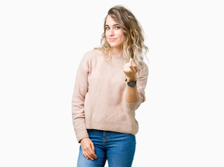 Beautiful young blonde woman wearing sweatershirt over isolated background Beckoning come here gesture with hand inviting happy and smiling