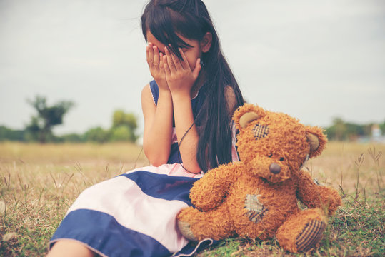 Sad child with Family problem,violence of parent is the one of divorce in bad relation family.Stress kid hugging teddy bear in park.Asian little girl sitting with best friends forever,cry moment.
