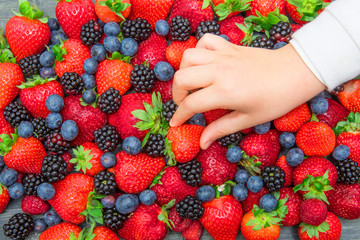 child's hand taking a strawberry from the group