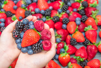 woman's hand holding delicious berry