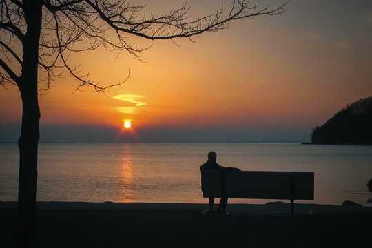 Blur background, no focusing -Abstract image for the background. A man sitting on a bench by the sea at sunset.